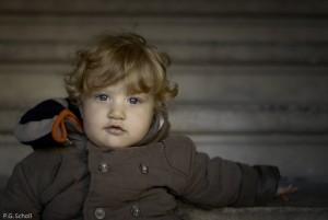 Petit blond aux yeux leus assis dans les escaliers.